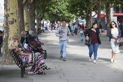 Folket promenerar bankerna av Themsen Lyckligt krama för par som sitter på en bänk Arkivfoto
