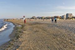 Folket promenerar den sandiga stranden i Rimini, Italien Royaltyfri Foto
