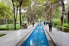 Folket promenerar diket med vatten i en parkera med högväxta forntida träd Arkivfoto