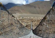 Folket promenerar en fot- upphängningbro över Kali Gandaki River Royaltyfria Foton