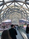 Folket promenerar en modern futuristisk fot- bro i centret Georgia Batumi, April 17, 2019 royaltyfri foto