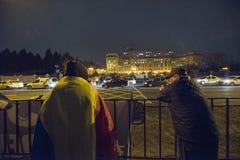 Folket protesterar framme av den rumänska parlamentet Royaltyfri Fotografi