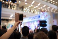 Folket räcker genom att använda smartphonen som tar fotoet i konsert Arkivfoto
