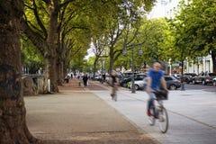 Folket rider cykeln i oskarp rörelse vid Konigsallee i Dusseldor fotografering för bildbyråer