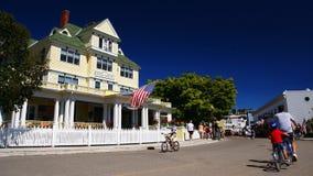 Folket rider cyklar för att se byn av den Mackinac ön fotografering för bildbyråer