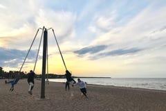 Folket rider karusellen på en sandig strand royaltyfri fotografi