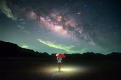 Folket rymde det orange paraplyet under stjärnafält Arkivfoto
