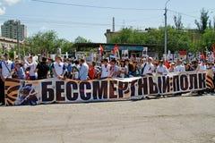 Folket rymmer banret av det odödliga regementet och stående av deras släktingar på segerdag i Volgograd Arkivbilder