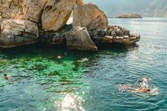 Folket simmar med turkosvatten för maskeringar utom fara av golfen av Oman arkivfoto