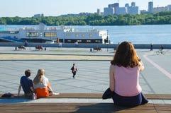 Folket sitter på en bänk på stranden royaltyfria foton