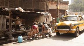 Folket sitter tillsammans på en bänk bredvid en taxi i en gata av Kolkata arkivfoto