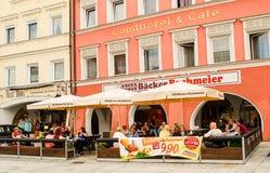 Folket sitter utanför en café på en solig eftermiddag Arkivbilder