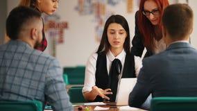 Folket sitter vid tabellen på kontoret och att diskutera deras arbete En ung kvinna som ger en rapport arkivfilmer