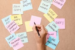 Folket skriver ner en viktig anmärkning som använder på de pappers- klistermärkearna, postar den arkivfoton