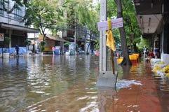 Folket skyddar deras hem, och affärer med sand hänger löst i en översvämmad gata av Bangkok, Thailand, på 30 November 2011 arkivfoton