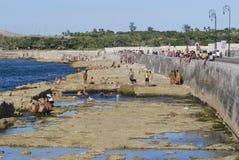 Folket solbadar på den Malecon skyddsmuren mot havet i havannacigarren, Kuba Arkivbild