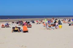 Folket solbadar på stranden, Nederländerna Royaltyfria Bilder