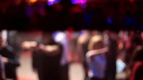 Folket som dansar ha gyckel och, kopplar av i en suddig bakgrund för nattklubb Härliga oskarpa ljus på dansgolvet, i mitten lager videofilmer