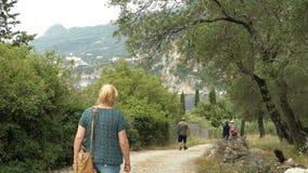 Folket som fotvandrar till och med olivgrön koloni i berg av Liapades på paradiset, sätter på land corfu greece stock video