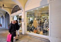 Folket som går av, shoppar framme fönster och att shoppa i den centrala portiken av det 16th århundradet Arkivbild