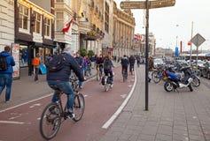 Folket som går och, rider cyklar i Amsterdam Arkivbilder
