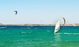Folket som gör kitesurf och, vindsurfar på den Naxos ön Cyclades Grekland Arkivbilder