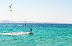 Folket som gör kitesurf och, vindsurfar på den Naxos ön Cyclades Grekland Royaltyfri Bild