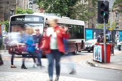 Folket som korsar övergångsställe i Edinburg som konungvägbussen, väntar på ljusen arkivbild