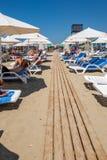Folket som ligger i sol, presiderar att solbada på en strand med en trästrandpromenad fotografering för bildbyråer