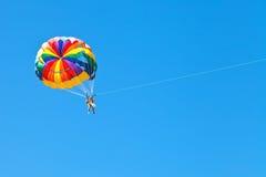 Folket som parascending på, hoppa fallskärm i blå himmel Arkivbild
