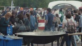 Folket som promenerar stort ånga för asiatisk gatamat, wokar på fullsatt parkerar festival lager videofilmer