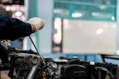 Folket som rymmer handen, reparerar ett motorcykelbruk en skiftnyckel och en skruvmejsel att arbeta royaltyfri foto