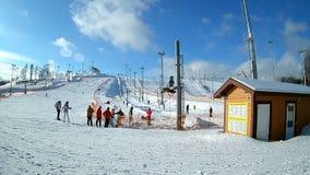 Folket som skidar på berglutningar skidar in, semesterorten, oigenkännliga skidåkare som tycker om vinteraktivitet på snö stock video
