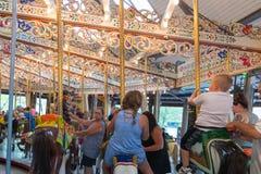 Folket som spelar ponnyn, rider på en karusellkarusell Arkivfoto