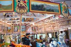 Folket som spelar ponnyn, rider på en karusellkarusell Royaltyfri Foto