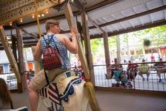 Folket som spelar ponnyn, rider på en karusellkarusell Royaltyfri Bild