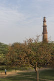 Folket som spelar syrsan i den arkeologiska mehraulien, parkerar och Qutub Minar som ses i bakgrund Royaltyfria Bilder