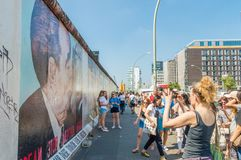 Folket som tar bilder av den Berlin väggen med att måla för grafitti som är bekant som min gud, hjälper mig att fortleva denna dö arkivbilder