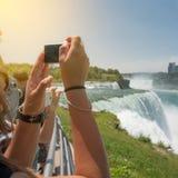 Folket som tar bilder under turisten, turnerar till Niagara Falls på den soliga sommardagen arkivbild