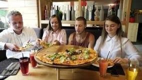 Folket som tar pizza, klipper från plattan på tabellen stock video