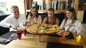 Folket som tar pizza, klipper från plattan på tabellen lager videofilmer