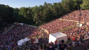Folket som utför den LaOla vågen i den slutsålda Waldbuehnen för ett pärlemorfärg driftstopp, vaggar konsert i Berlin - öppen luf stock video