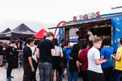 Folket som väntar i linje för att köpa hamburgare från en mat, åker lastbil Fotografering för Bildbyråer