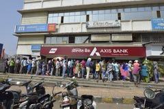 Folket som väntar utanför axelbanken för att återta och den gamla insättningen, drar in gamla mynt indisk valuta i Bombay, mahara Royaltyfria Bilder