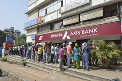 Folket som väntar utanför axelbanken för att återta och den gamla insättningen, drar in gamla mynt indisk valuta i Bombay, mahara Arkivfoton