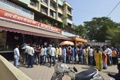 Folket som väntar utanför Icici banken för att återta och den gamla insättningen, drar in gamla mynt indisk valuta i Bombay, maha Royaltyfri Bild