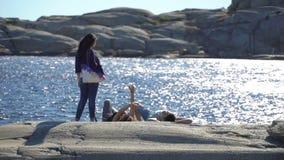 Folket som vilar på stenar i den Tjome naturen, parkerar på sydkusten av Norge lager videofilmer