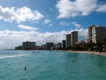 Folket spelar i det skyddade vattnet och hänger ut på stranden in royaltyfri fotografi