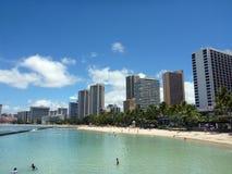 Folket spelar i det skyddade vattnet och hänger ut på stranden in arkivfoton