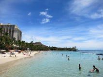Folket spelar i vattnet och hänger ut på stranden i världsfamo royaltyfria foton